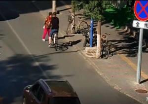 男子骑车看手机,撞上前面的老太太